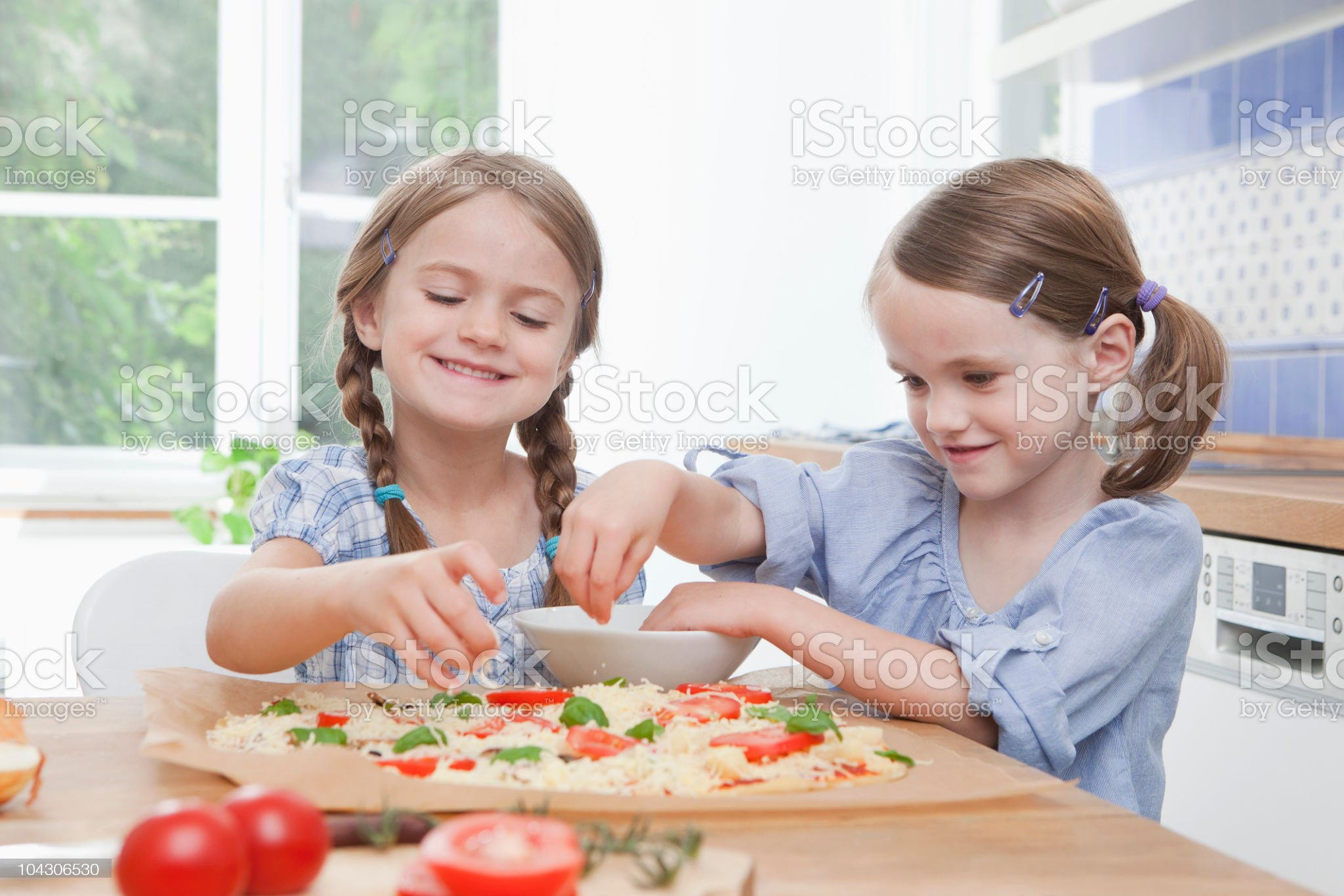 Germany, Munich, Girls (4-7) preparing food in kitchen royalty-free stock photo