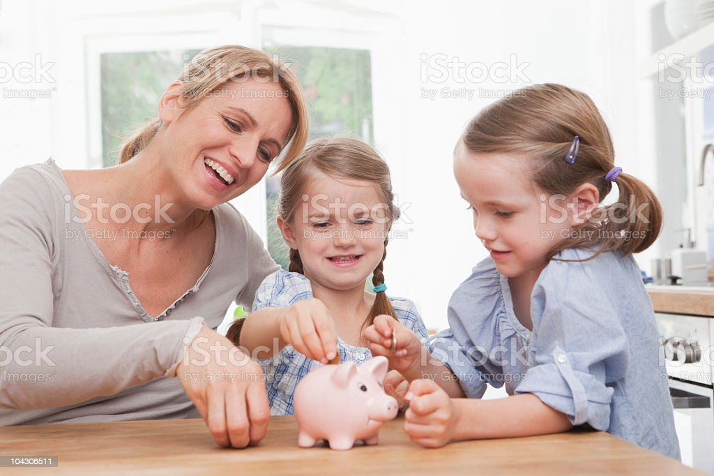 Germany, Munich, Mother and daughters (4-7) putting coins in piggy bank royalty-free stock photo