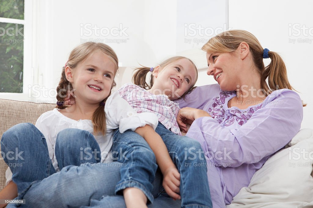 Germany, Munich, Mother with daughters (4-7) resting on sofa royalty-free stock photo