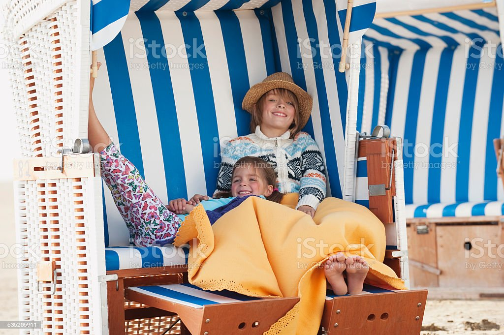 Germany, St.Peter-Ording, North Sea, Children resting on hooded beach chair stock photo