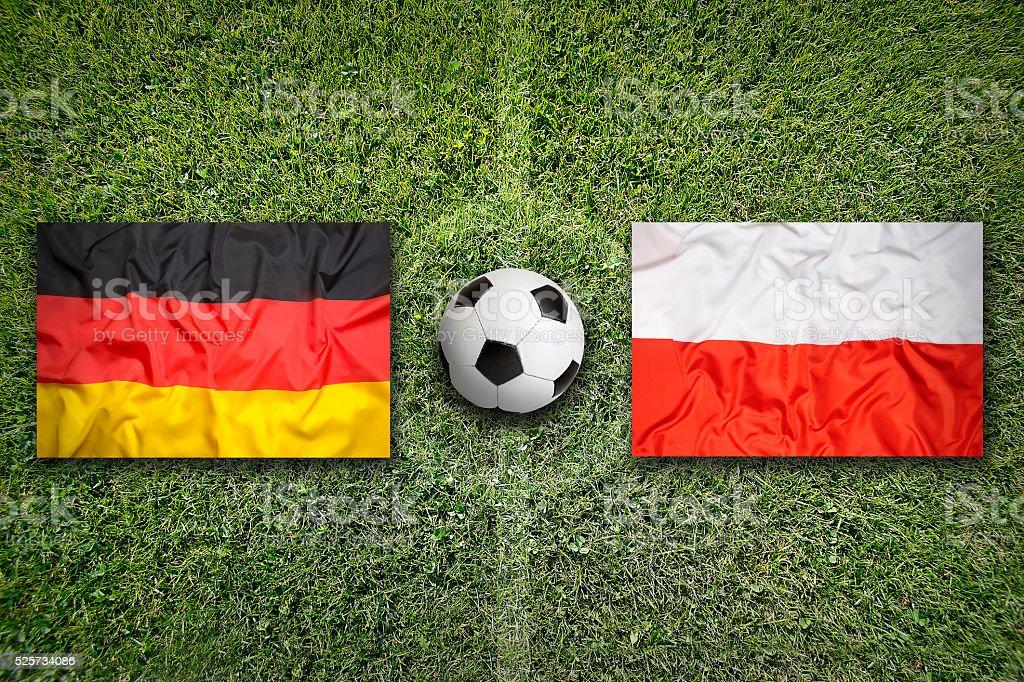 Germany vs. Poland flags on soccer field stock photo