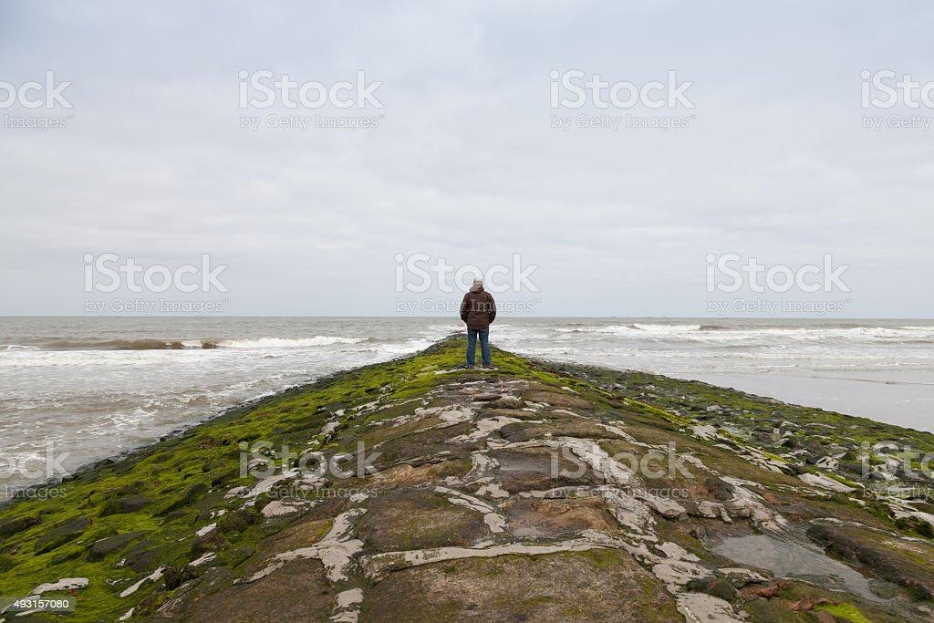 Germany, Wangerooge, North Sea, one man on breakwater stock photo