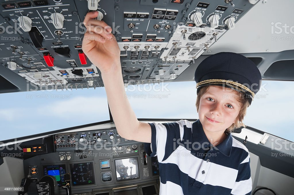 Germany,Bavaria,Munich,boy wearing captain's hat and playing in stock photo