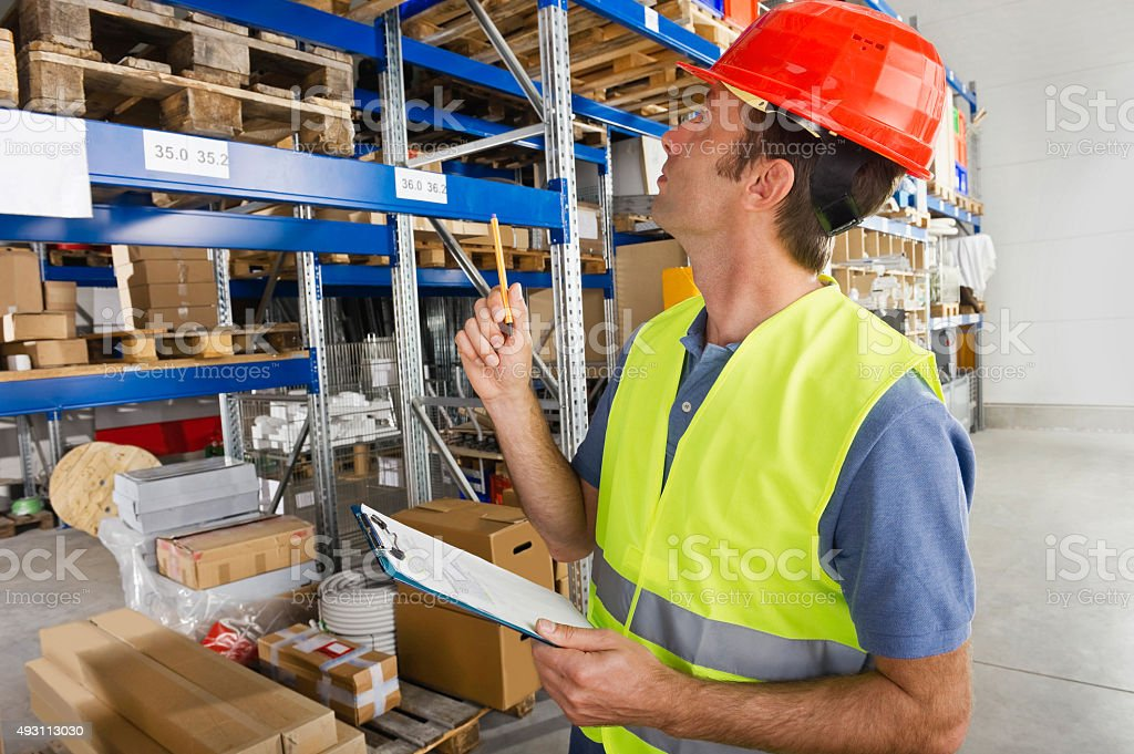 Germany,Bavaria,Munich,Manual worker with clipboard in warehouse stock photo