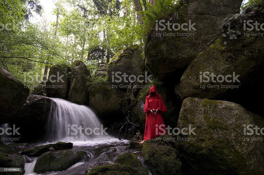 Gesichtslose rote Zauberin am mystischen Wasserfall royalty-free stock photo
