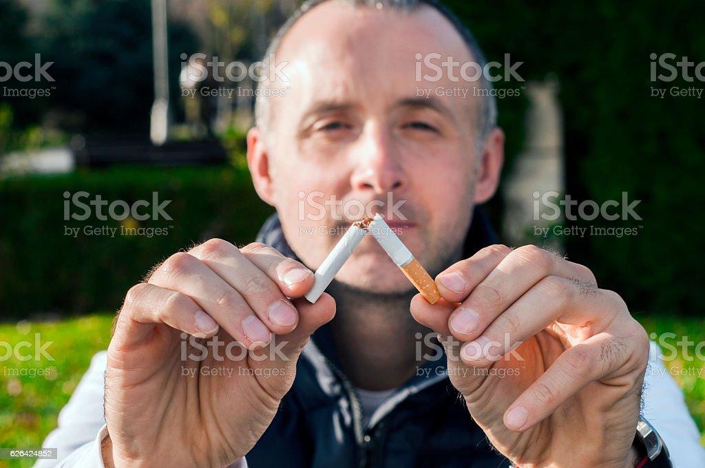 Gesture for quit smoking, Anti Smoking,  male hand crushing cigarette stock photo