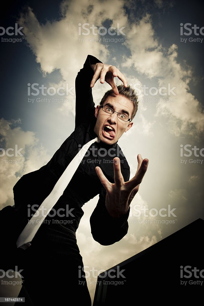 Gesturing and wildly grimacing young businessman sticking out tongue royalty-free stock photo