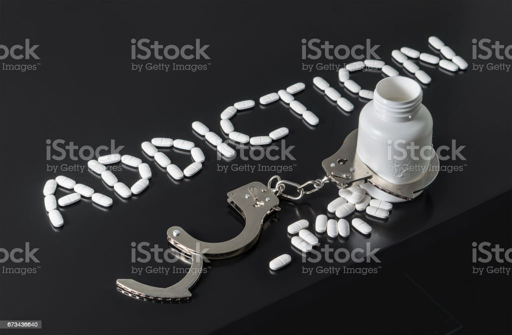Get addicted to drugs or free from addiction to medicine. Drug and narcotics abuse or after rehab concept. Medicine spilling out from a bottle locked with open handcuffs. stock photo