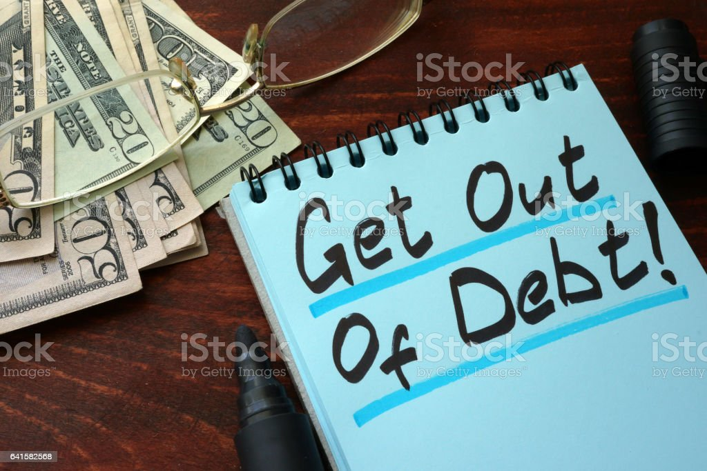 Get out of Debt written on a notepad with marker. stock photo