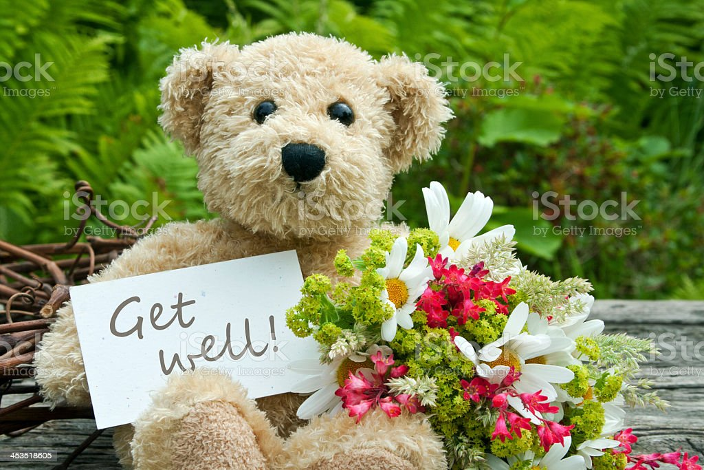 Get well soon teddy bear with flowers stock photo