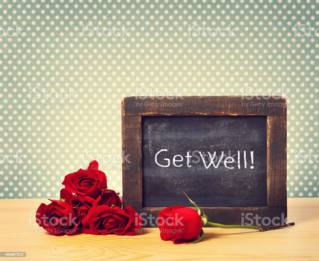 Get Well Text on Small Chalkboard with Red Roses stock photo