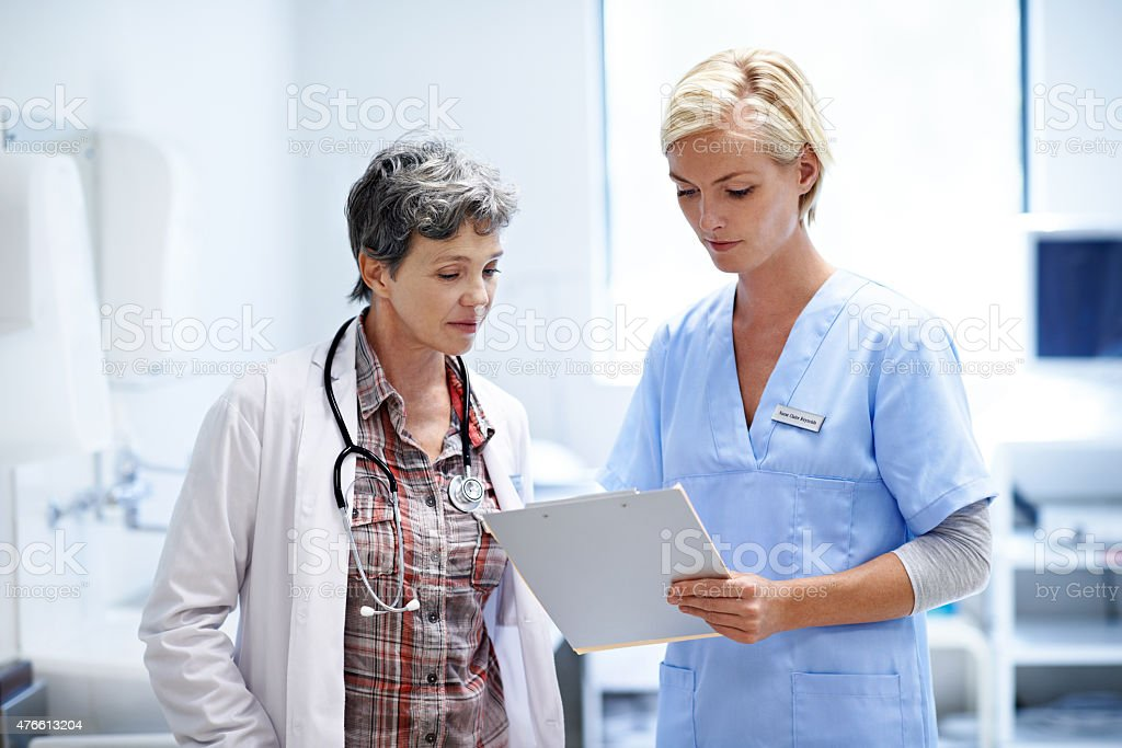 Shot of two female doctors looking through a medical report together...