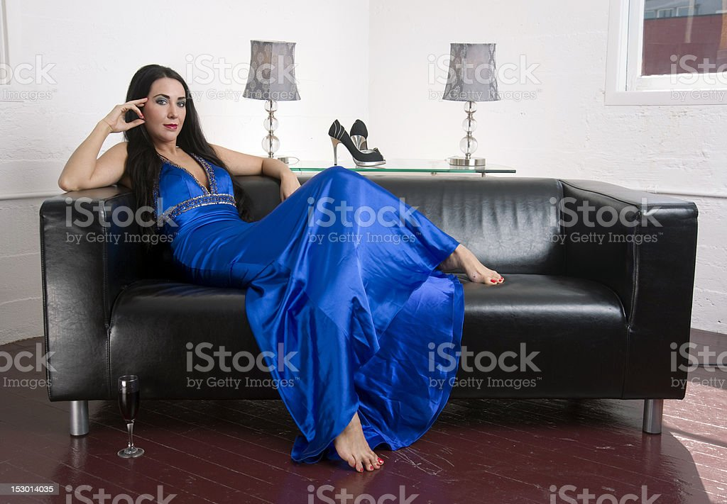 Getting Comfortable Barefooted Brunette Woman in Blue Dress Leather Couch royalty-free stock photo