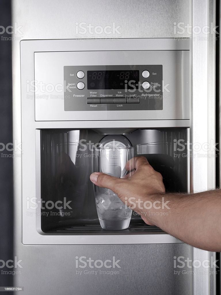 Getting glass of filtered water from refrigerator. stock photo