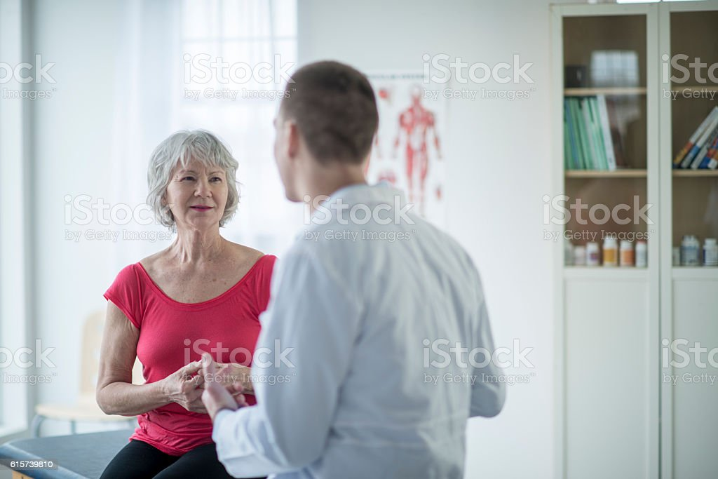 A physical therapist helps an older woman with stretches, therapy...