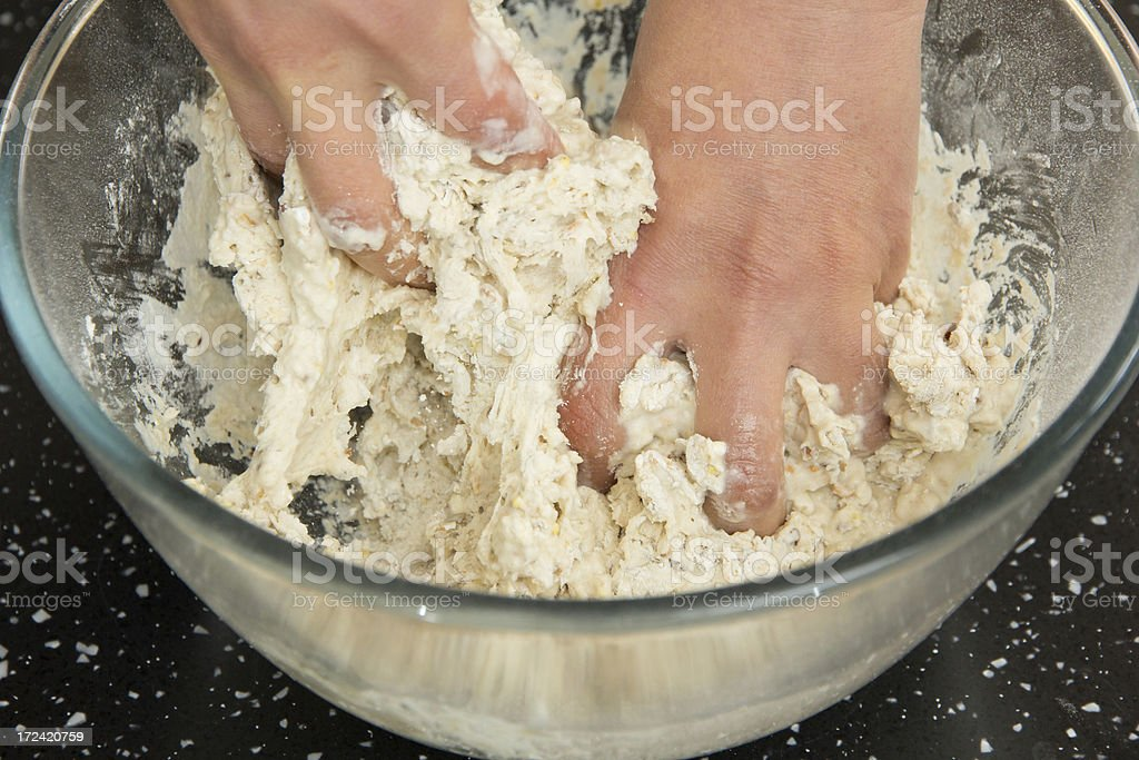 Getting hands messy mixing bread dough stock photo