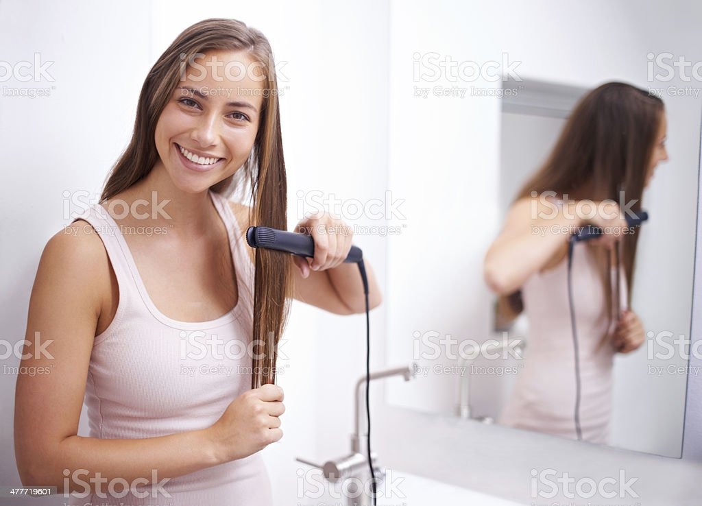 Getting her hair perfectly straight royalty-free stock photo