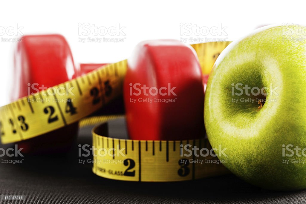 Getting in shape with weights, tape measure and healthy apple royalty-free stock photo