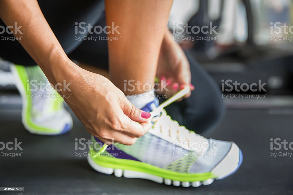 Getting ready to run, but first tying sport shoe stock photo
