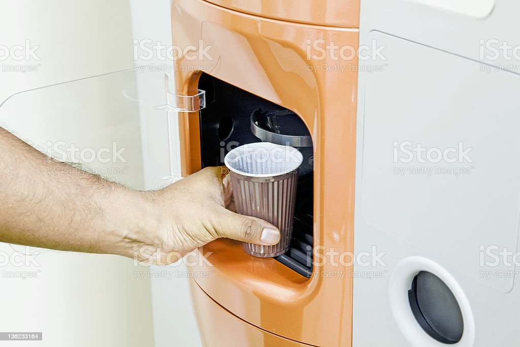 Getting some fresh coffee out of a machine stock photo