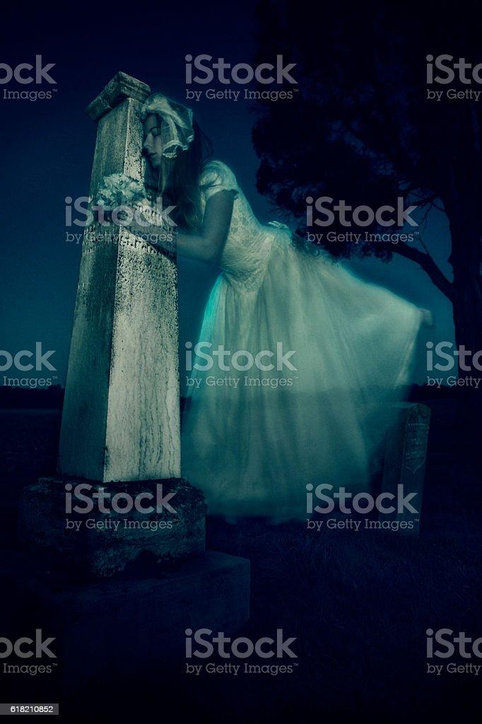 Ghost bride in vintage wedding dress hugs headstone stock photo