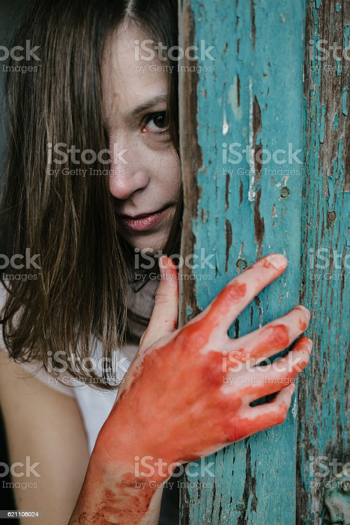 Ghost woman behind vintage wooden door, blood covered hand stock photo