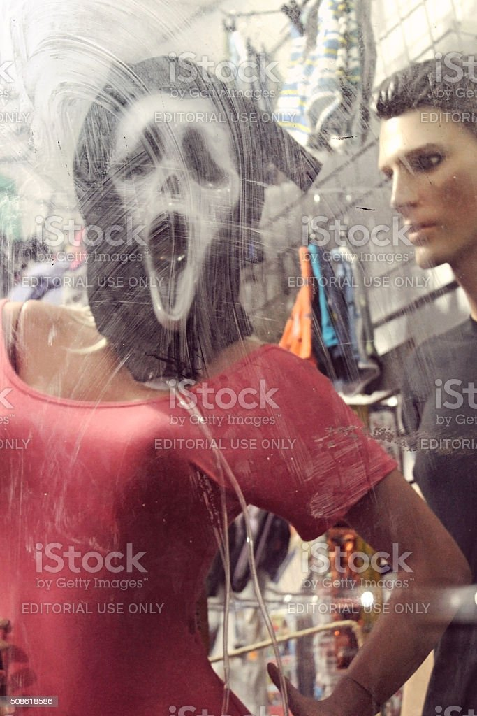 Ghostface 'Scream' Mask Behind Dirty Glass stock photo
