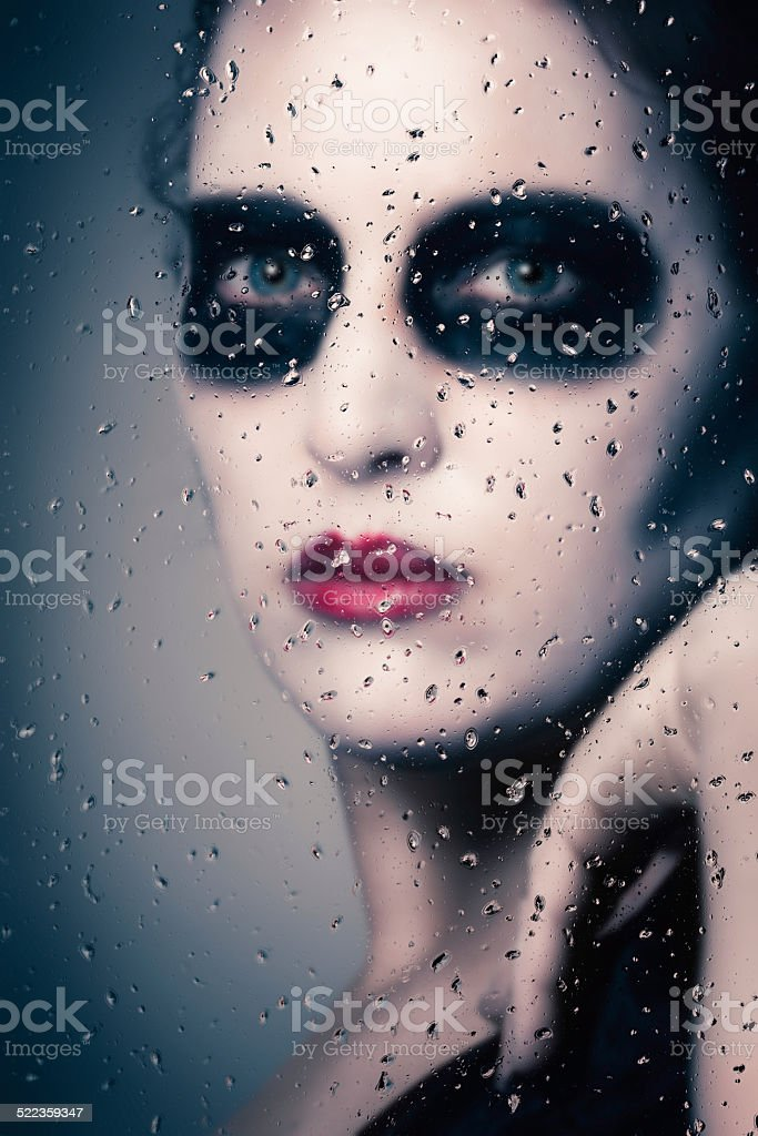 ghostly face behind wet glass stock photo