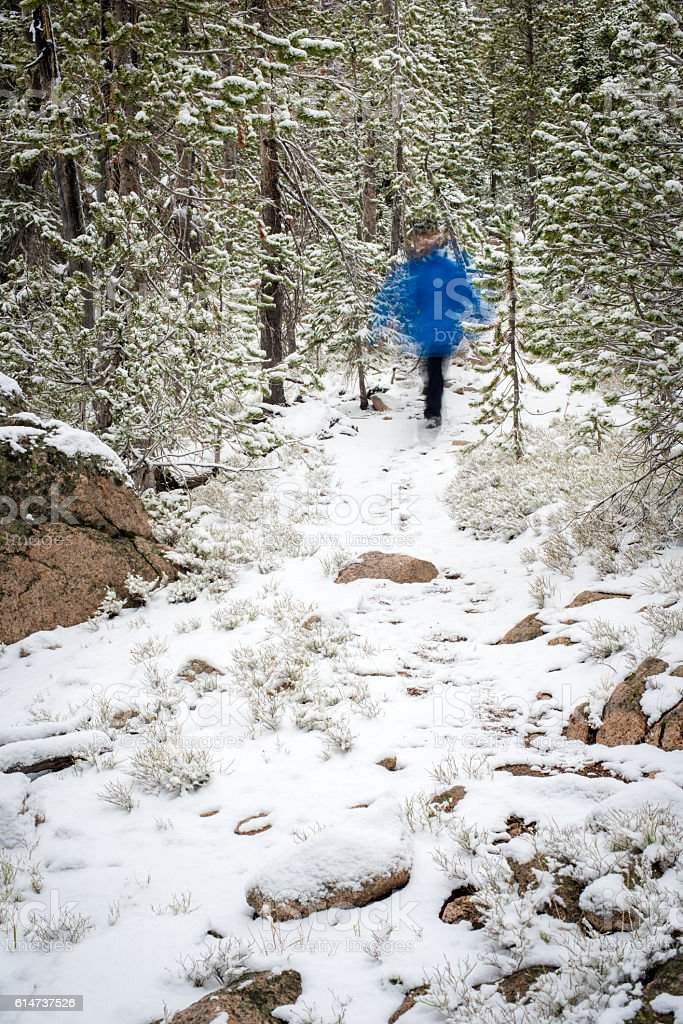 Ghostly figure hikes down a winter trail stock photo