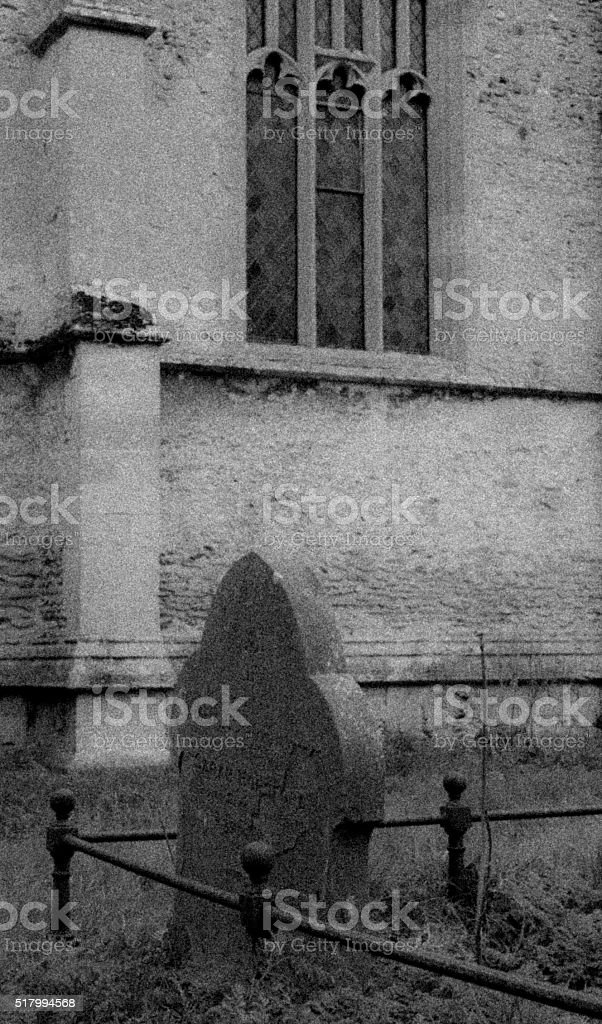Ghostly image of an old grave in front of a chapel stock photo