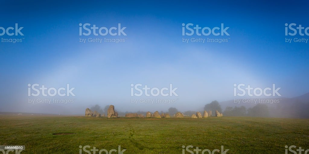 Ghostly white bow shines above Castlerigg stone circle stock photo