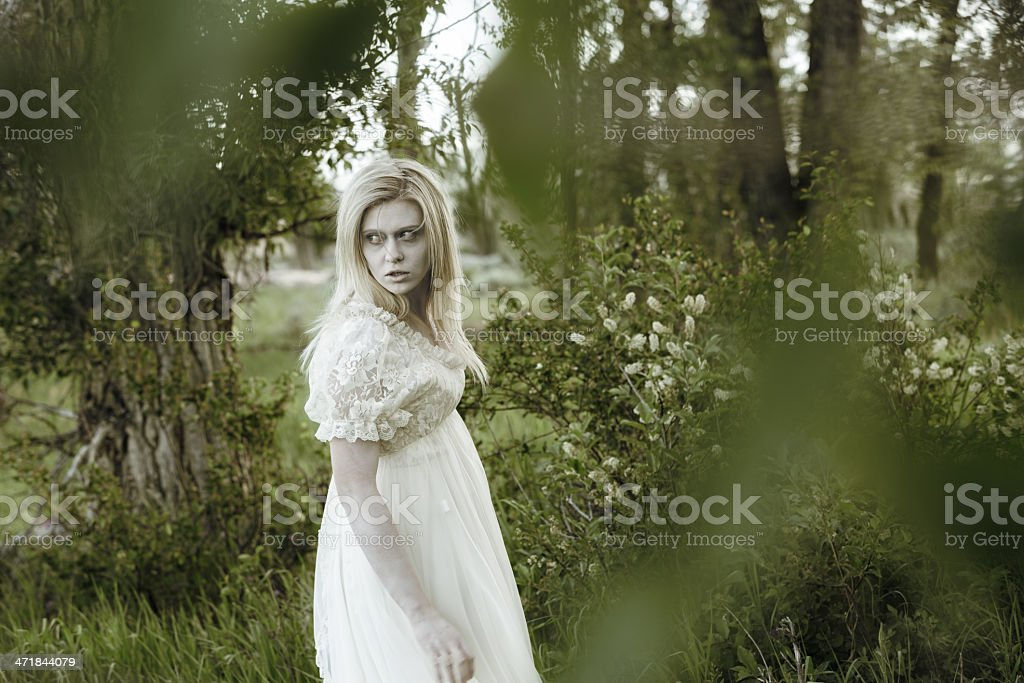 Ghostly woman walking through heavily wooded area royalty-free stock photo