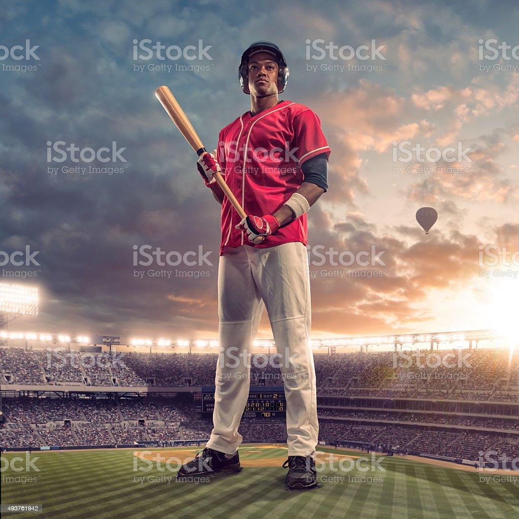 Giant Baseball Batter Standing in Floodlit Soccer Stadium At Sunset stock photo