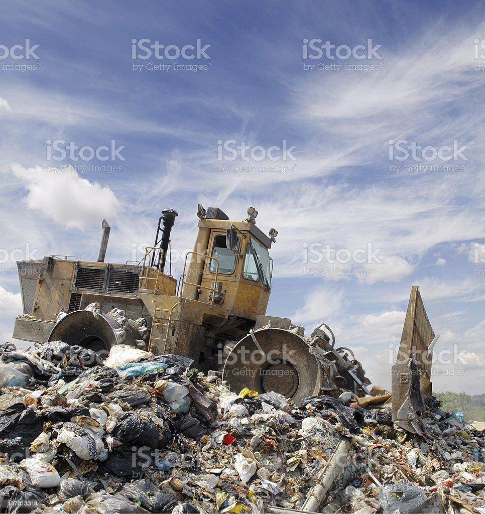 Giant bulldozer destroying garbage at the dump stock photo