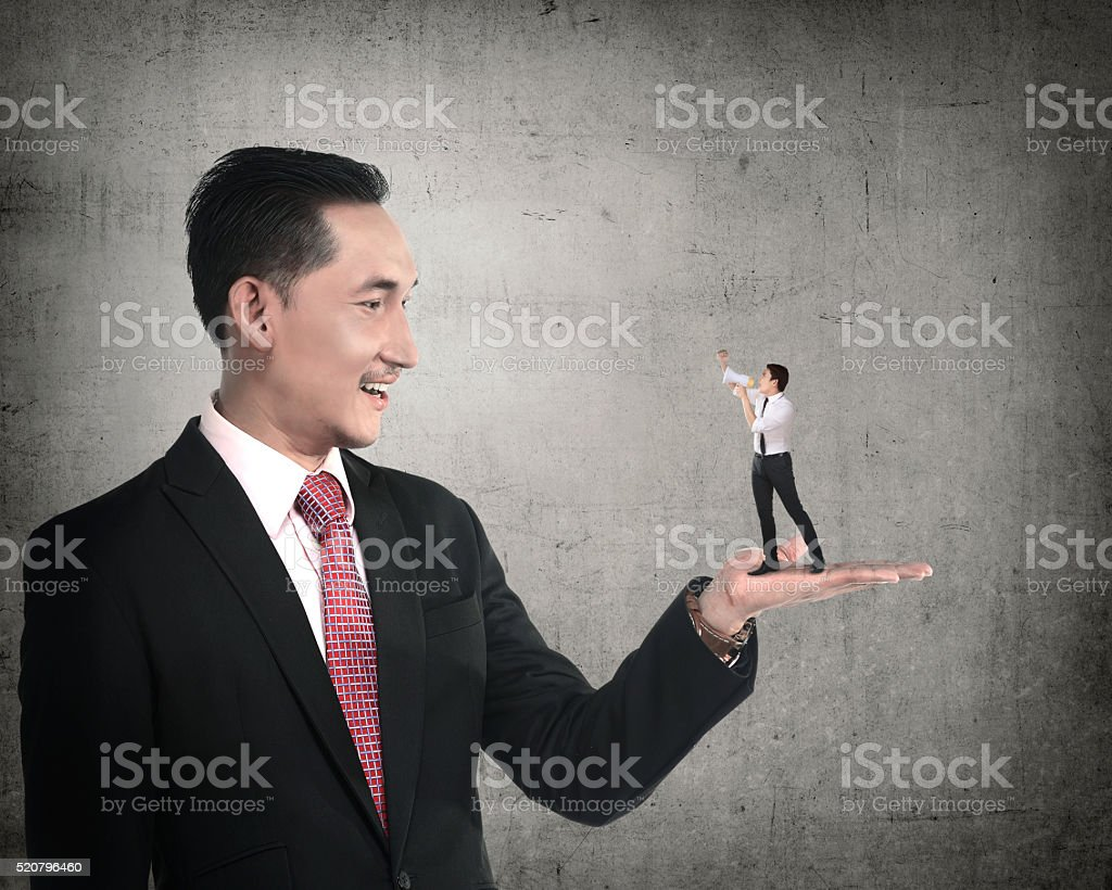 Giant businessman holding little man yelling with megaphone stock photo
