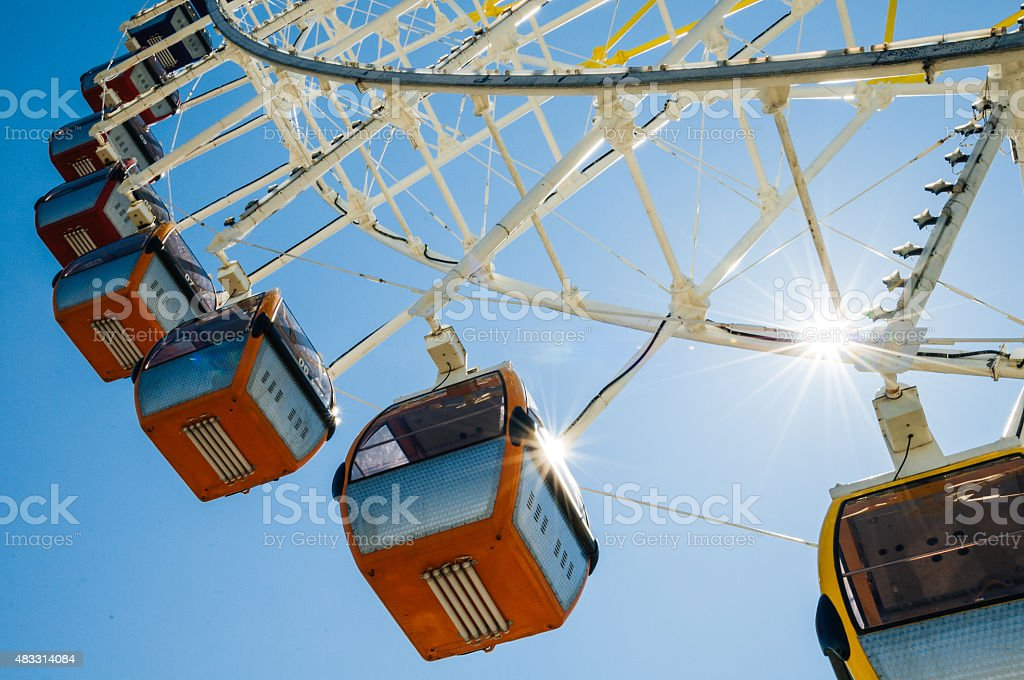 Giant ferris wheel on sunny day against blue sky stock photo