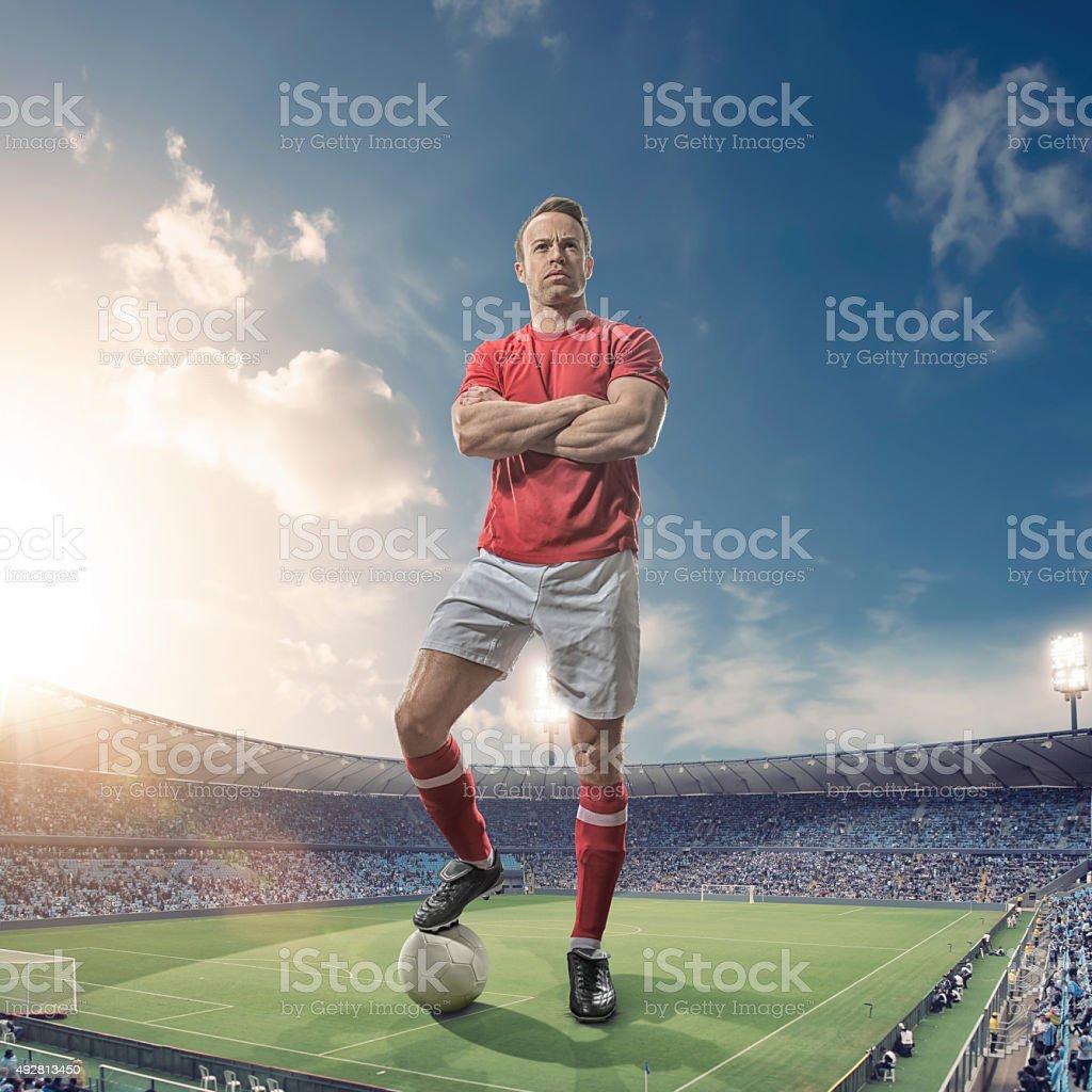 Giant Footballer Standing in Floodlit Soccer Stadium At Sunset stock photo