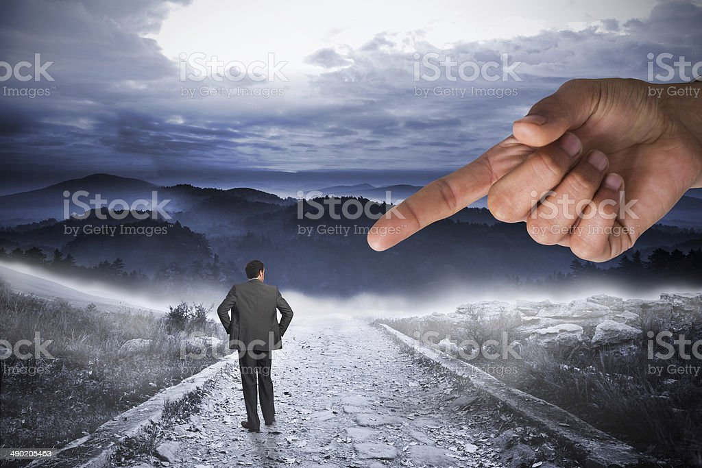 Giant hand pointing at businessman with hands on hips stock photo