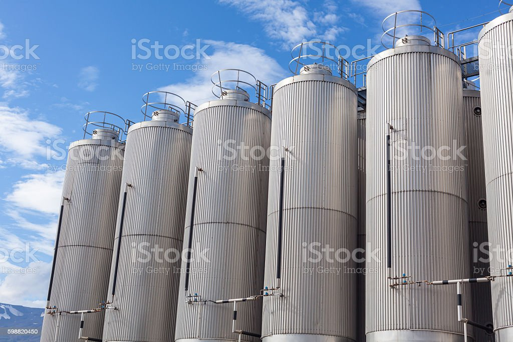 Giant industrial tanks on the bright blue sky stock photo