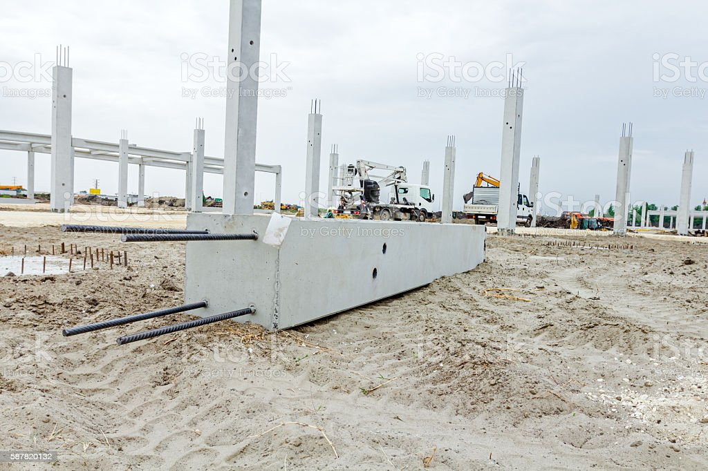 Giant reinforced concrete column is placed on sandy ground stock photo