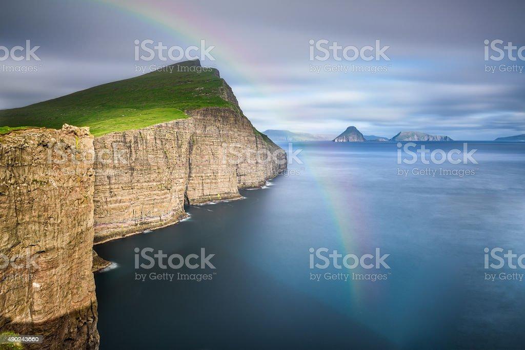 Giant sea cliffs on Faroe Islands with a rainbow stock photo