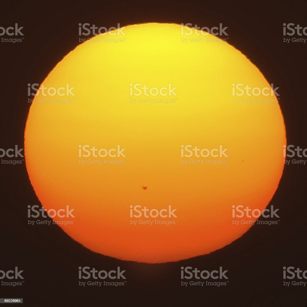 Giant setting sun with sunspot stock photo