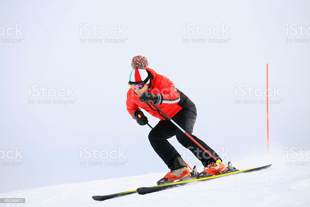 Giant slalom race. Mature Men skier, snow skiing carving at high...