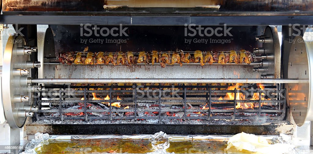 giant spit full of cockerels and roast chickens stock photo