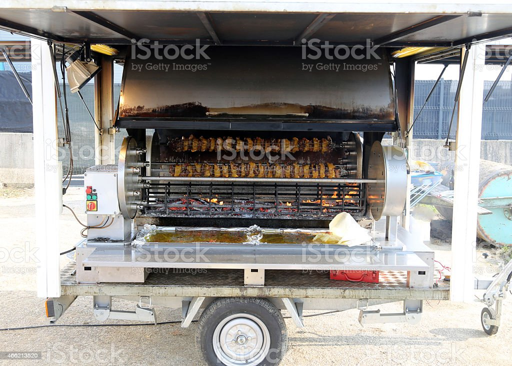 giant spit with wheels full of cockerels and roast chickens stock photo