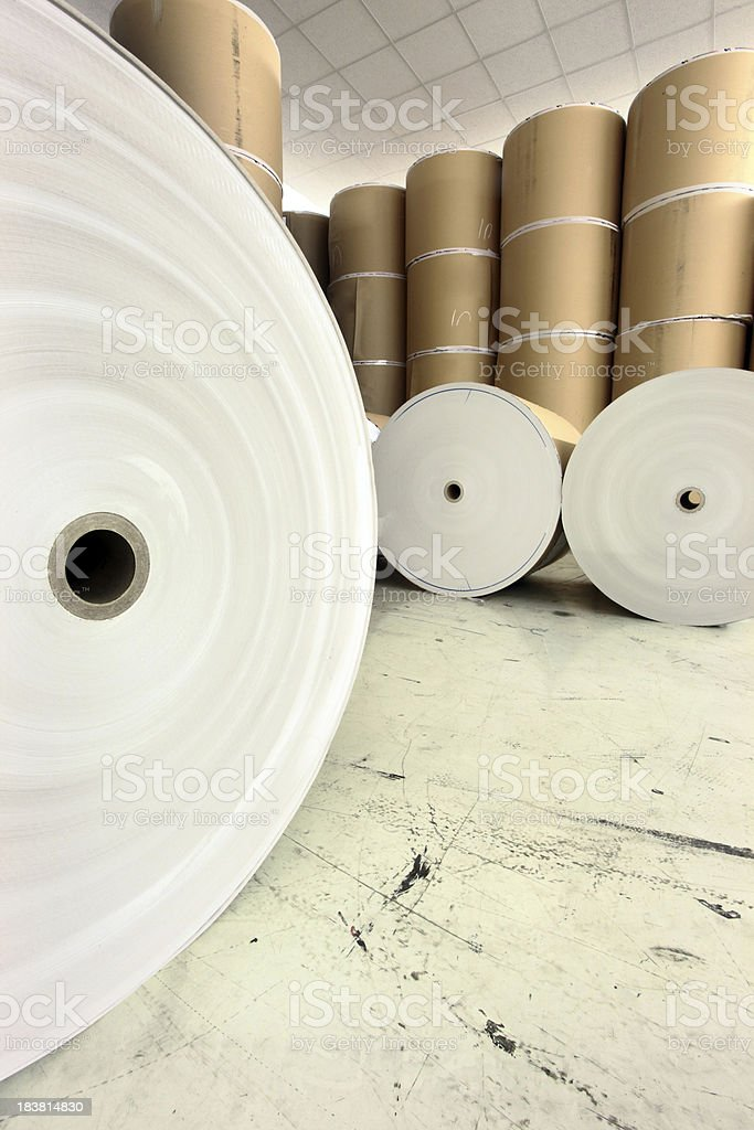 Giant spools of raw paper stacked in a warehouse stock photo