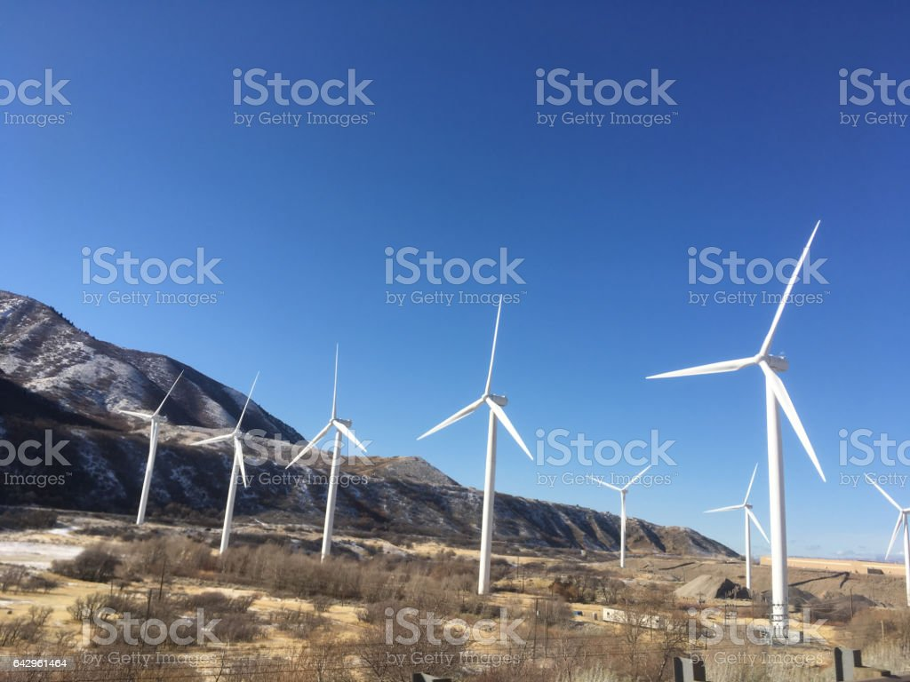 Giant wind turbines create clean, renewable energy.  Blue skies and mountains.  Spanish Fork Canyon, Spanish Fork, Utah, USA. Utah green energy production. stock photo