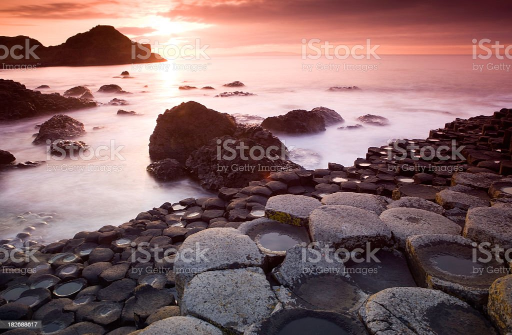 A Giants Causeway with fog on the ground during sunrise stock photo