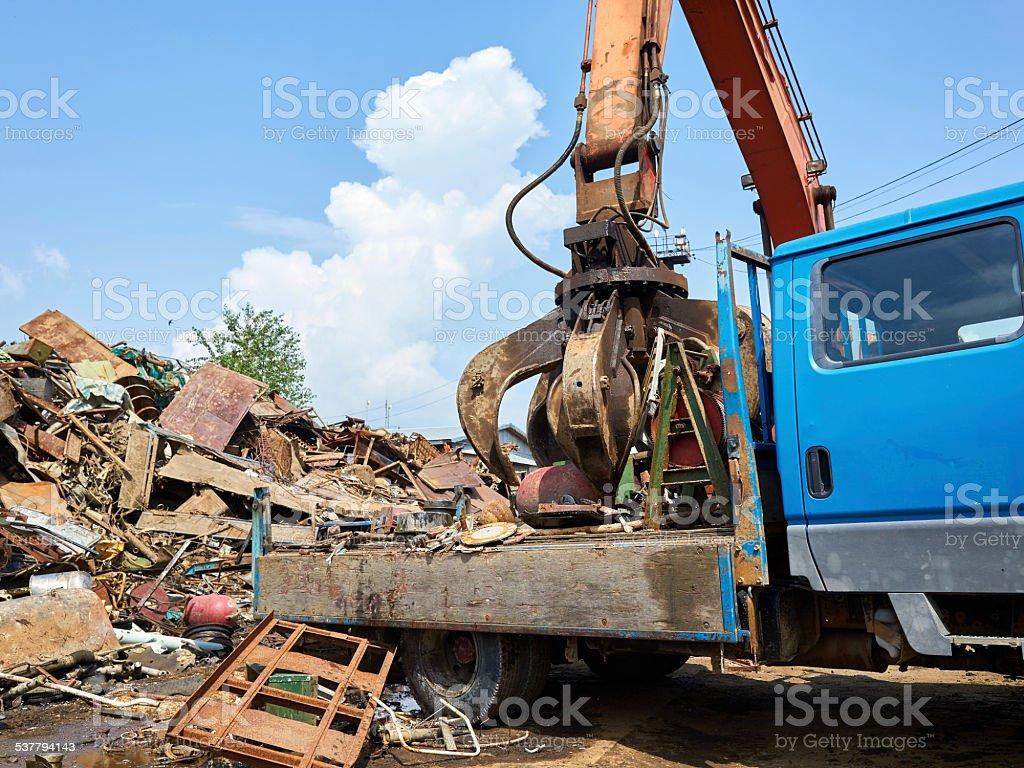 Gidraulic mechanical grabber moves scrap rusty metal heap stock photo