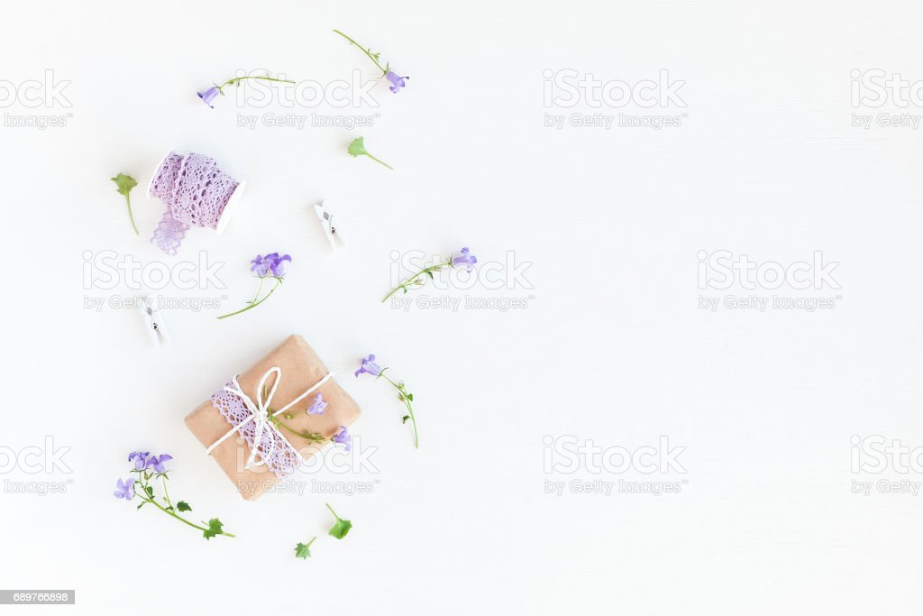 Gift and bell flowers on white background. Flat lay stock photo